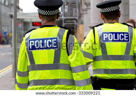 Two police officers in hi-visibility jacket patrolling in the city. British Police officers