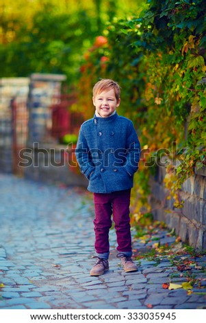 cute fashionable boy walking on autumn street #333035945