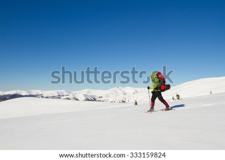 Winter hiking in the mountains on snowshoes with a backpack and tent. #333159824