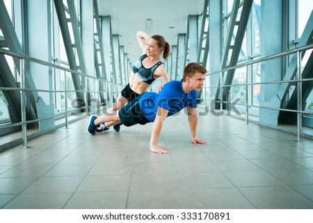 young man and woman doing exercises in the modern bridge construction #333170891