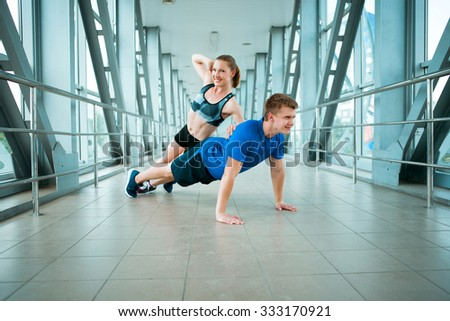 young man and woman doing exercises in the modern bridge construction #333170921