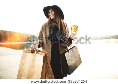 Attractive cute girl in with the shopping bags and warm drink in her hand #333204254