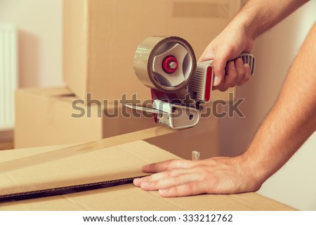 Close up of a guy's hands holding packing machine and sealing cardboard boxes with duct tape Royalty-Free Stock Photo #333212762