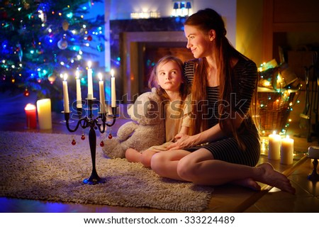 Young mother and her little daughter sitting by a fireplace in a cozy dark living room on Christmas eve #333224489