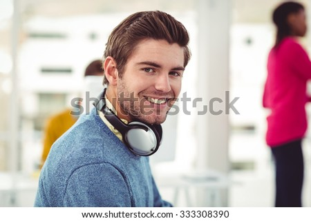 Graphic designer wearing headphones at desk in casual office #333308390