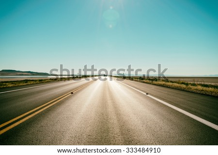 Asphalt road to the horizon line under a burning Sun Royalty-Free Stock Photo #333484910