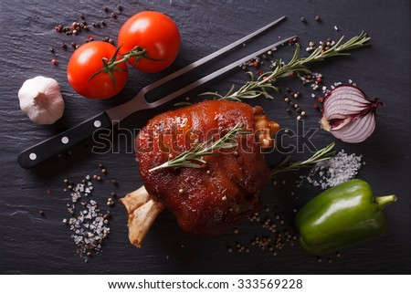 Baked pork shank, vegetables and spices close-up on a slate board. Horizontal top view #333569228