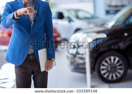 car agent  in car dealership saloon holding car key in front of him #333589148