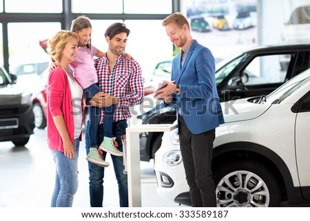 Car dealer offering a car to young  smiling family #333589187