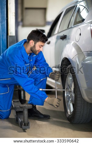 Uniform mechanic working on tyre in garage #333590642