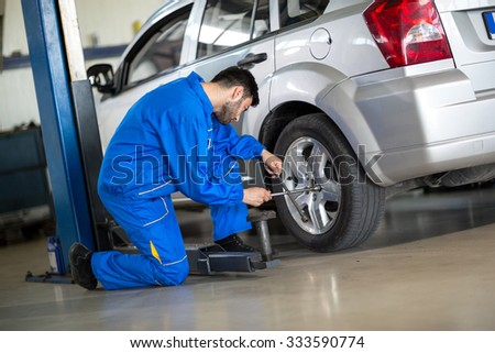 Mechanic change tyre on car #333590774