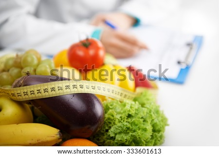Healthy nutrition concept. Close-up of fresh vegetables and fruits with measuring tape lying on doctor's desk.  Royalty-Free Stock Photo #333601613