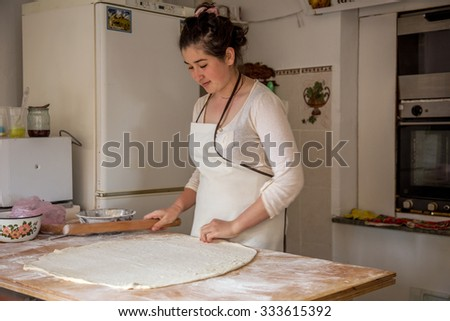 Sudak, RUSSIA - May 15 2015: Young beautiful girl rolled the dough and prepare the national Crimean Tatar meal pasties in a small kitchen, a fast food restaurant. Crimean - Tatar national cuisine #333615392
