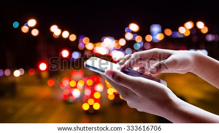 Girl use smart phone , Blur of lights from cars at night on the road, a very beautiful bokeh are on background. #333616706