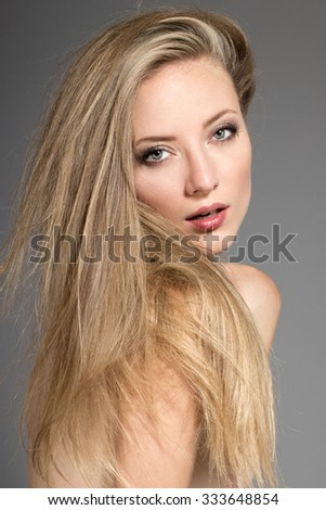 Awesome caucasian attractive sexy professional fashion model with blond hair posing in studio topless, perfect make up, tanned skin, isolated on gray background, retouched image
