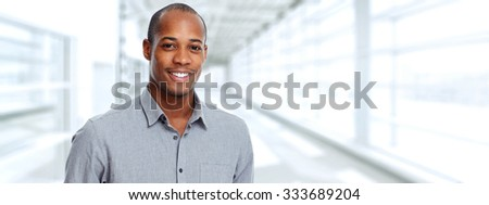 Young smiling African-american businessman over office background. #333689204