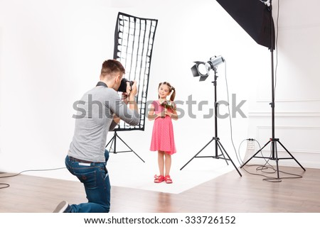 Photoshoot in progress. Young handsome male photographer in the process of taking photos of small model girl.
