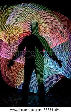 Black silhouette in front of abstract freezelight color background. Lightsaber drawing. #333811691