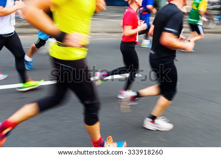 picture with creative motion blur effect made by camera of running people at a city marathon #333918260