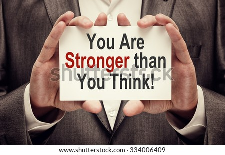 You Are Stronger Than You Think ! Motivational Message written on a card in hands of a businessman #334006409