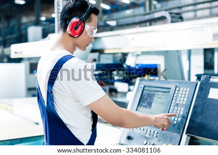 Worker entering data in CNC machine at factory floor to get the production going #334081106