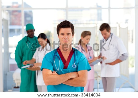 Cofident doctor with his team in the background in hospital #33414004