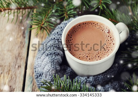 Cup of hot cocoa or hot chocolate on knitted background with fir tree and snow effect, traditional beverage for winter time #334145333