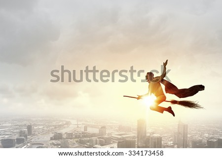 Young businessman flying high above city on broom #334173458
