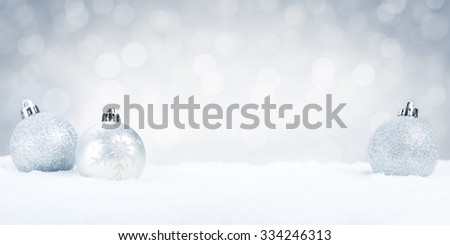 Silver Christmas baubles on snow with defocused silver and white lights in the background. Shallow depth of field.