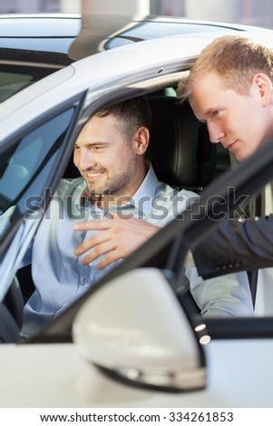 Picture of pleased male client testing luxurious white car #334261853