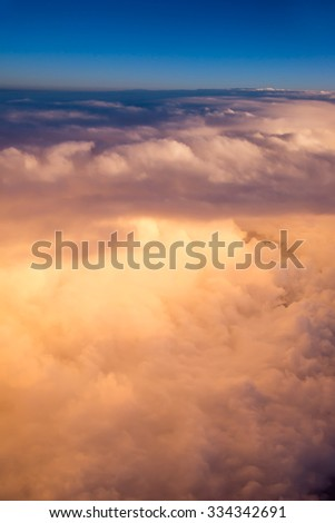 View of the sky and clouds from the airplane porthole at sunset #334342691