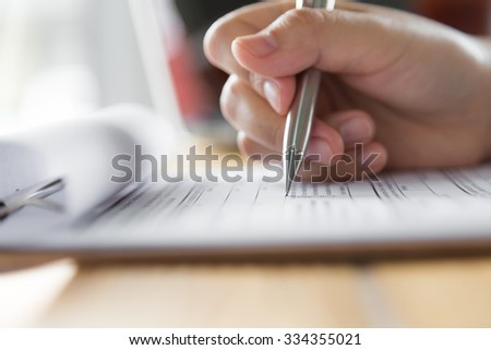 Hand with pen over application form #334355021