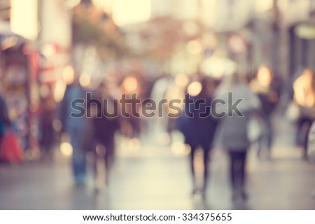 Blurred background. Blurred people walking through a city street. Toned photo.