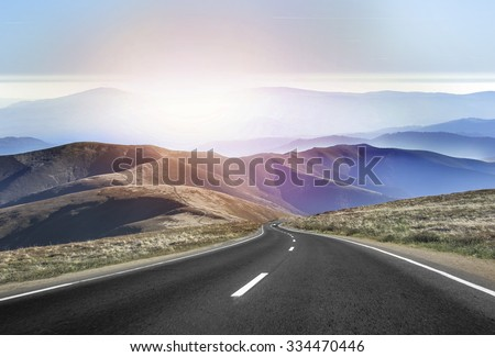 Asphalt road in the mountains with soft sky on the background. #334470446