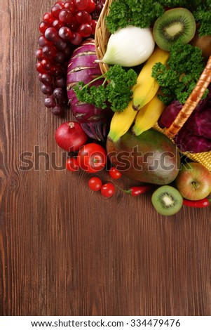A set of fruit and vegetables in a basket on wooden background #334479476