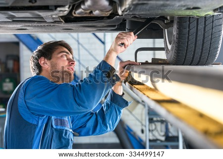 Mechanic, examining the suspension of a vehicle with a steel rod for any undesired clearances as part of a periodical vehicle safety inspection or mot test #334499147