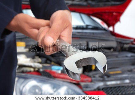 Hands of car mechanic with wrench in auto repair service.  #334588412