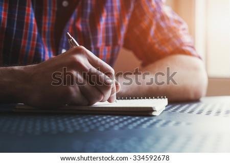 male hand writing in notebook with pen #334592678