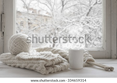 Cozy winter still life: mug of hot tea and warm woolen knitting on vintage windowsill against snow landscape from outside. #334659314