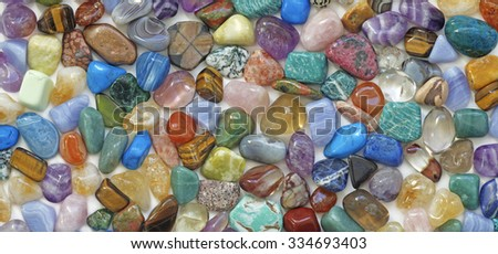 Multicolored tumbled crystal stones background - a large quantity of different colored healing tumbled gem stones making up a backdrop for use as a background