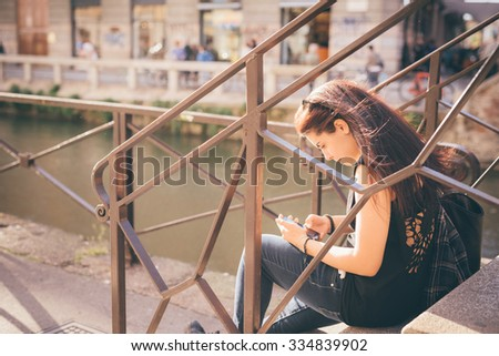 Young handsome caucasian reddish brown hair woman seated on a staircase using a smartphone - technology, social network, communication concept - dressed with black shirt and blue jeans #334839902