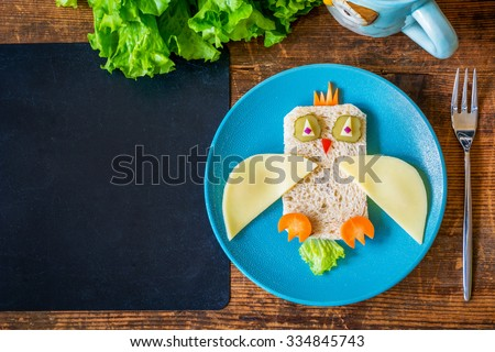 Healthy school lunch for kids. Funny owl sandwich and salad on wooden table plus empty black chalkboard for text. Copy space, table top view