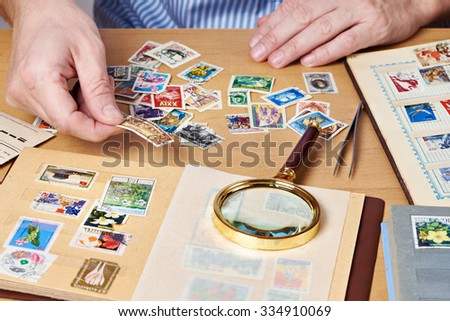 Man watching a collection of postage stamps isolated #334910069