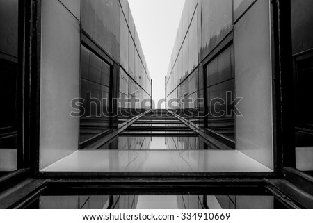 Urban Geometry, looking up to glass building. Modern architecture, glass and steel. Abstract architectural design. Inspirational, artistic image. Industrial design. .Modern building. Black and white. Royalty-Free Stock Photo #334910669