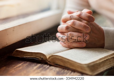 Unrecognizable woman holding a bible in her hands and praying Royalty-Free Stock Photo #334942220