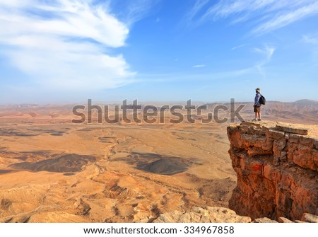 Panoramic view of color stone desert of Negev and traveler on the mountain top. National geological park HaMakhtesh HaGadol - Large Crater - a geological erosion land form, Israel #334967858