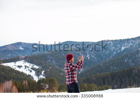 man in shirt and hat on the phone taking pictures in the mountains in winter
