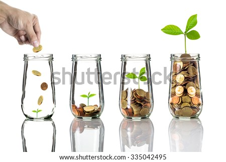 Hand putting gold coins into clear bottle on white background,Business investment growth concept Royalty-Free Stock Photo #335042495