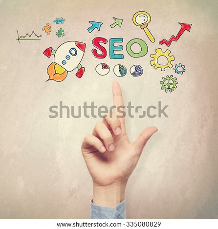 Hand pointing to SEO concept on light brown wall background #335080829