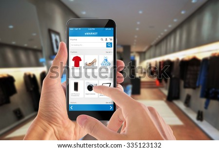 Smart phone online shopping in man hand. Shopping center in background. Buy clothes shoes accessories with e commerce web site Royalty-Free Stock Photo #335123132